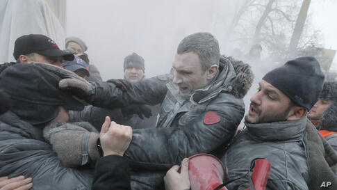Opposition leader and former WBC heavyweight boxing champion Vitali Klitschko, center, is attacked and sprayed with a fire extinguisher as he tries to stop the clashes between police and protesters in central Kyiv, Ukraine.