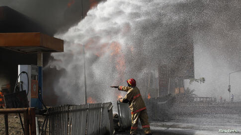 A firefighter standing near a Conoil petrol filing station directs his colleagues as to which direction to apply their hose, during a fire opposite the Nigeria National Petroleum corporation (NNPC) headquarters in Abuja.