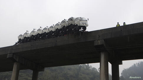 A trailer loaded with trucks hangs on the edge of the guardrail on a bridge in Kaili, Guizhou province, China, Oct. 21, 2013. According to local media, the trailer hanged on the edge of the bridge after the driver lost control of the vehicle. No injury...
