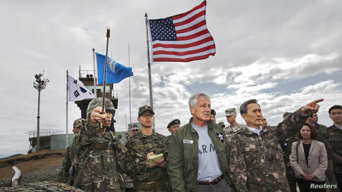 South Korean Defense Minister Kim Kwan-jin (R) points out a location in North Korea to U.S. Secretary of Defense Chuck Hagel, from Observation Point Ouellette during a tour of the Demilitarized Zone (DMZ), South Korea.