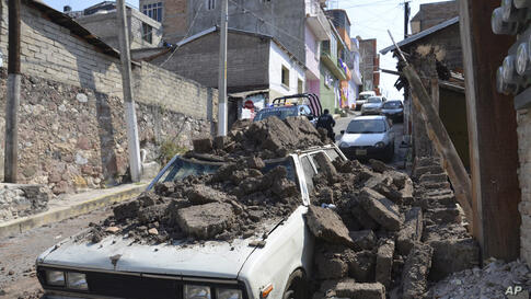 A parked car suffered damage when a adobe wall collapsed on it after a strong earthquake shook Chilpancingo, Mexico.