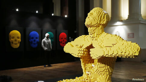 "The art work titled ""Yellow,"" which is made out of Lego bricks, is seen next to another Lego art work titled ""Skulls"" (L) during ""The Art of the Brick"" exhibition at the Brussels Stock Exchange, Belgium."