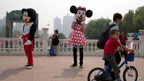 A Minnie Mouse look-alike mascot waits to greet visitors to a park in Beijing, China.