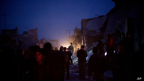 People near a damaged building after it was attacked by a Syrian Army jet in Azaz, Syria, December 16, 2012.