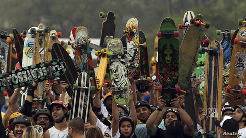 Skateboarders raise their skateboards as they line up at the starting line of the Skate Run competition in Sao Paulo, Brazil, Sept. 22, 2013.