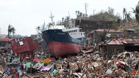 A ship lies on top of damaged homes after it was washed ashore by Typhoon Haiyan in Tacloban city, Leyte province, central Philippines. The city remains littered with debris from damaged homes as many complain of shortages of food and water and no elec...