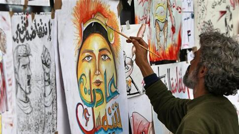 """An artist paints a poster with writing in Arabic reading """"Egypt, your golden sun has returned"""", on the front of a closed fast food outlet, in a street which has become a meeting point and workshop for artists to create political posters, at the continuing"""