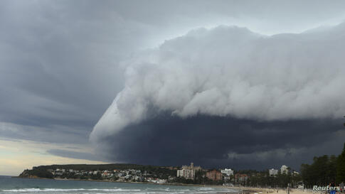 A wave-like cloud looms over Sydney's Manly Beach, Australia, during an afternoon storm front. The storm, which generated little rain, was blown out to sea.