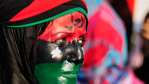 "June 29: A woman with her face painted in the colours of the Kingdom of Libya flag attends a protest against Muammar Gaddafi near the court house in Benghazi. The word on her forehead reads, ""Leave"".  (Reuters/Esam Al-Fetori)"
