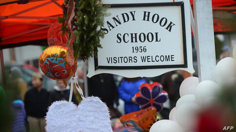 A pair of angel wings and balloons stand after being offered at a makeshift shrine to the victims of a elementary school shooting in Newtown, Connecticut, December 16, 2012.