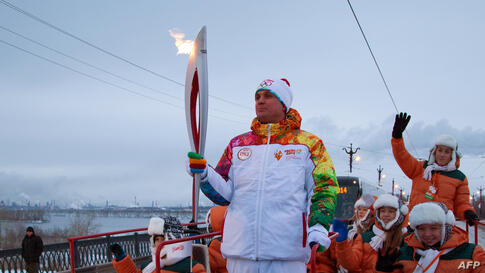 A handout picture taken during the Sochi 2014 Winter Olympic torch relay shows Russian torchbearers carrying the torch ahead of Winter Games in Sochi in Moscow, Russia, Dec. 18, 2013.