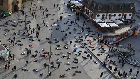 "People lay down in a pedestrian zone as part of an art project in remembrance of the 528 victims of the ""Katzbach"" Nazi concentration camp, in Frankfurt, Germany, Mar. 24, 2014. The inmates of the Katzbach concentration camp, a part of the former Adler..."