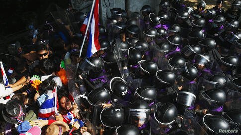 Anti-government protesters clash with riot police during a mass rally outside the house of Thai Prime Minister Yingluck Shinawatra in Bangkok in a bid to topple her before an uncertain February election the main opposition party will boycott.