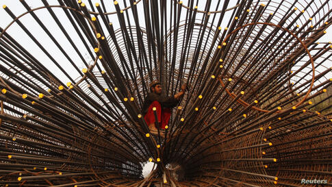 A laborer works on the scaffoldings of a flyover under construction in Lahore, Pakistan.
