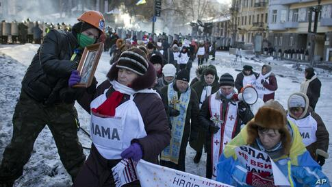 """Protesters, with signs reading """"Mother"""" on their chests, and """"""""The government don't kill our children,"""" walk away from a police cordon in central Kyiv, Jan. 30, 2014."""