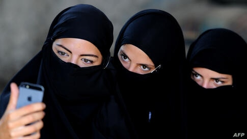 """Georgian actors take a group selfie wearing veils before taking part in a joint Georgian-U.S. military counterterrorism exercise called """"Agile Spirit 2014"""" at the Vaziani military base outside Tbilisi."""