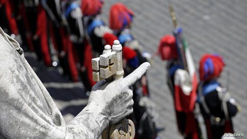 Italian Carabinieri paramilitary police stand at attention as Saint Peter's statue is seen in the foreground on Saint Peter's Square before an audience led by Pope Francis at the Vatican.
