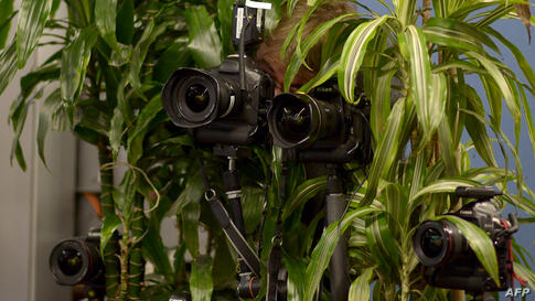 A photographer looks through his camera amidst other cameras set up to document German Chancellor and Christian Democratic Union candidate (CDU) Angela Merkel at a polling station in Berlin, Sept. 22, 2013.