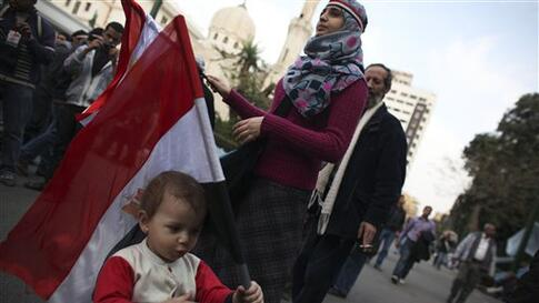 An anti-government protester stands with her daughter as they carry Egyptian flags outside the Egyptian Parliament in Cairo, Egypt, Wednesday, Feb. 9, 2011. Around 2,000 protesters waved huge flags outside the parliament, several blocks from Tahrir Square
