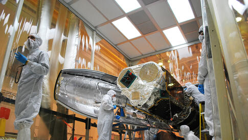 Technicians install one half of the payload fairing over the NuSTAR spacecraft as they continue to process the spacecraft and its Pegasus rocket for launch, May 22, 2012. (NASA)
