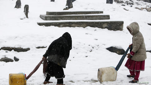 Children drag water containers as it snows in Kabul, Afghanistan.