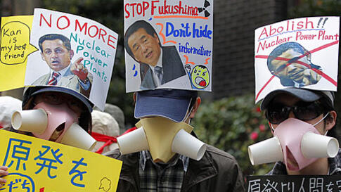 Protesters hold placards condemning the use of nuclear power at a rally in Tokyo, Sunday, April 10, 2011, after a devastating earthquake and tsunami crippled the Fukushima Daiichi nuclear complex in northeastern Japan last month