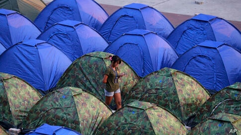 An anti-government protester checks message from her mobile phone in the middle of tents at a rally site in Bangkok, Thailand.