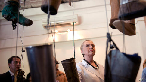 Clinton, center, watches an exhibition of artificial limbs on her tour at the Cooperative Orthotic Prosthetic Enterprise Center (COPE), in Vientiane, Laos, July 11.