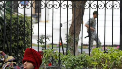 An anti-government protester sits behind a bush as an Egyptian soldier walks in the background, outside the Egyptian Parliament in Cairo, Egypt, Wednesday, Feb. 9, 2011. Around 2,000 protesters waved huge flags outside the parliament, several blocks from
