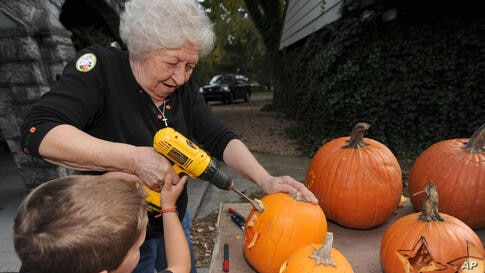 Betty Dillow helps her grandson with his pumpkin carving in Bristol, Virginia.