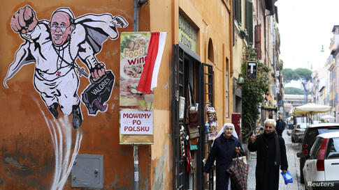 A priest and a nun walk by a large drawing of Pope Francis that depicts him as a superhero on a wall near the Vatican.