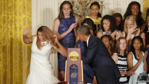 U.S. President Barack Obama hugs UConn women's basketball coach Geno Auriemma as team star Stefanie Dolson (L) falls off the stage in the background during a ceremony honoring the NCAA basketball champion University of Connecticut Huskies men's and wo...
