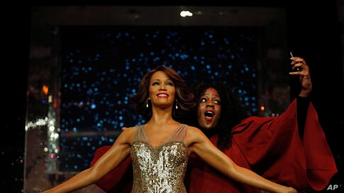 A member of a gospel choir pretends she takes a picture of herself with the wax figure of late U.S. singer Whitney Houston, as she poses for the photographers at Madame Tussauds in London, Britain.