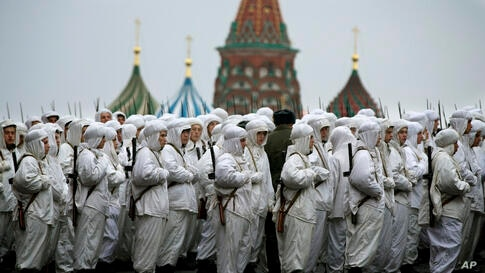 Russian soldiers wear snow gear over Red Army World War II uniforms as they prepare to parade in Red Square in front of St. Basil Cathedral in Moscow, Russia. Thousands of soldiers and military cadets marched across Red Square to mark the 72nd annivers...