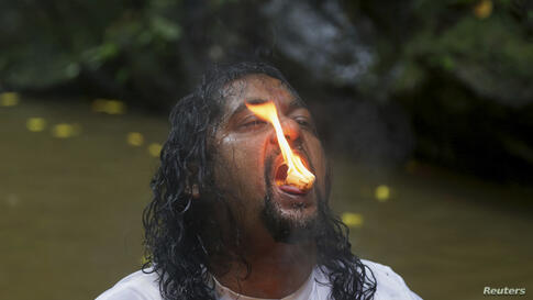 Camphor burns on the tongue of a devotee as he participates in the Ganga Dhaaraa festival at Marianne River, Blanchisseuse on Trinidad's north coast, June 8, 2014. Pilgrims all over the country and abroad have been gathering for the Hindu festival, als...