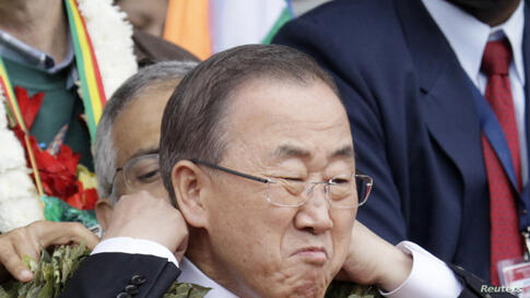 United Nations Secretary-General Ban Ki-moon adjusts his garland made with coca leaves during a welcome ceremony for delegates of the G77+ China Summit at Tahuichi Aguilera Stadium in Santa Cruz de la Sierra, Bolivia, June 14, 2014.