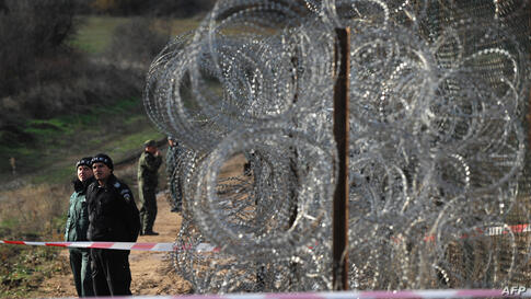 Border police stand guard next to a border fence being built on the Bulgarian border with Turkey, near the village of Golyam Dervent. Bulgaria, the European Union's poorest member, has been overwhelmed by the arrival this year of almost 10,000 refugees...