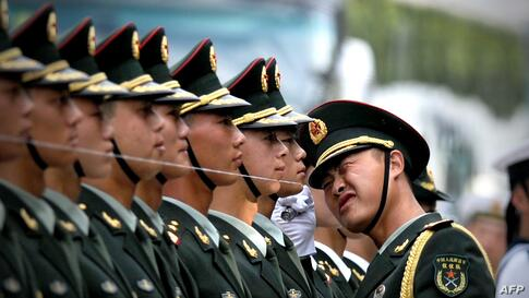 Chinese honor guards prepare for the arrival of Myanmar (also known as Burma) President U Thein Sein and Chinese President Xi Jinping during a welcome ceremony outside the Great Hall of the People in Beijing. A string is set up to ensure members of the...