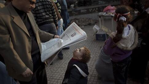 A boy looks at a newspaper in Tahrir Square, Cairo, Egypt, Wednesday, Feb. 9, 2011. Protesters appear to have settled in for a long standoff, turning Tahrir Square into a makeshift village with tens of thousands coming every day, with some sleeping in ten