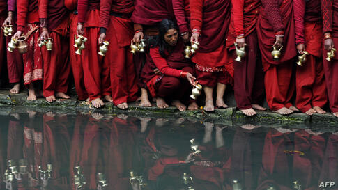 Nepalese Hindu devotees wait to fill pots with water from the Bagmati River at the Pashupatinath Temple during the month-long Swasthani festival in Kathmandu. Scores of married and unmarried women in the Himalayan nation are marking the month-long fast...