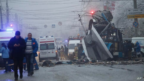 Ambulances line up at the site of a trolleybus explosion, background, in Volgograd, Russia. A bomb blast tore through the trolleybus in the city, killing at least 10 people a day after a suicide bombing that killed at 17 at the city's main railway stat...