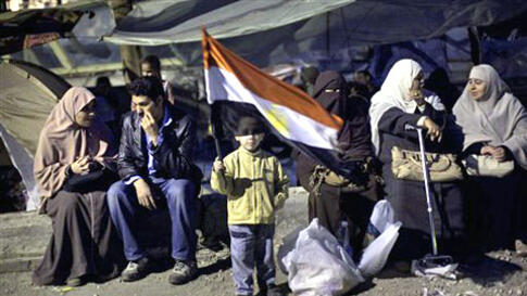 A boy holds an Egyptian flag next to anti-Mubarak protesters at Tahrir Square in Cairo, Egypt, February 6, 2011