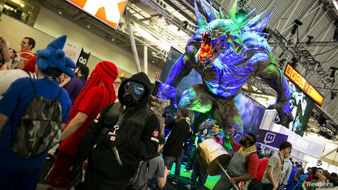 A monster character from the game Evolve looms over gaming enthusiasts at the PAX East convention in Boston, Massachusetts, April 12, 2014.