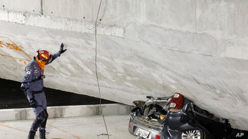 A policeman looks at a car crushed underneath a collapsed bridge in Belo Horizonte, Brazil, July 3, 2014.