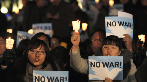 People hold signs at a candlelight vigil calling for peace on the Korean peninsula, in Seoul November 29. South Korean President Lee Myung-bak vowed retaliation against any further provocation by the North after it attacked an island last week.  (Kim Kyun