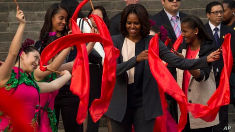 U.S. first lady Michelle Obama (c) dances with performers during her visit to Mutianyu section of the Great Wall of China in Beijing with her daughters Malia (2nd left), and Sasha (r).