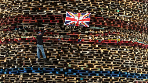A man gestures as he climbs wood stacked for a bonfire on the Shankill Road in West Belfast, Northern Ireland.