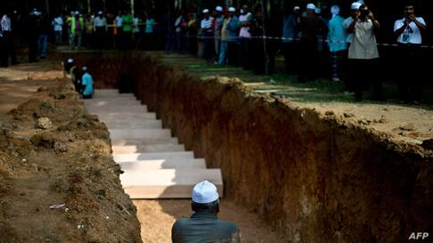 A Malaysian Muslim man sits near a pit during the re-burial of remains believed to be those of ethnic Rohingya found at human-trafficking camps in Kampung Tualang, some 16 kilometers east of Alor Setar. Authorities held a sombre mass funeral for 21 sus...