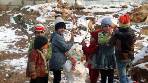 Syrian refugees children play near a snowman in a camp for Syrians who fled their country's civil war, in the Bekaa valley, eastern Lebanon.