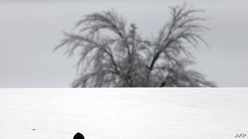 Caelan Brooks, 12, glides down a hill at Hoblitzelle Park in Plano, Texas. The ice storm left over 250,000 residents and businesses without power and has led to more than 1,700 flight delays and cancellations across the country.